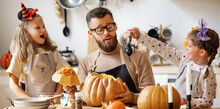 Bearded Man And Girls With Jack O Lantern Smiling And Scare Each Other With A Spider  During Preparation For Halloween Celebration In Kitchen At Home