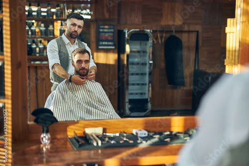 Fototapeta Young hair specialist putting a barber cape on his visitor