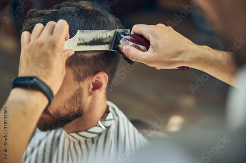 Fototapeta Skillful hair-stylist using electric hair clipper to cut hair