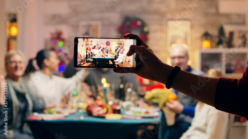 Fototapeta Girl taking a family portrait with her phones while celebrating christmas. Traditional festive christmas dinner in multigenerational family. Enjoying xmas meal feast in decorated room. Big family obraz
