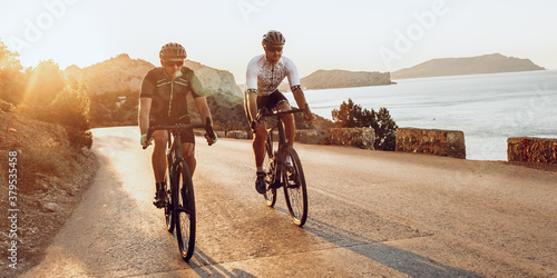 Two professional male cyclists riding their racing bicycles in the morning together
