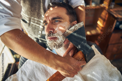 Handsome young man being shaved with an axe Canvas Print