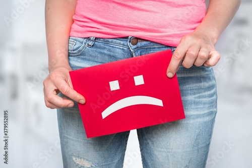 Woman with incontinence problem with sad smiley on paper