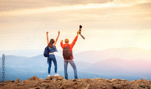 Foto Happy travelers couple conquered top of mountain, raises hands up with camera an