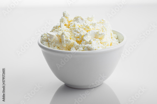 Foto in a white plate, crumbly cottage cheese on an isolated white background