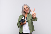 Middle Age Woman Smiling And Looking Happy, Carefree And Positive, Gesturing Victory Or Peace With One Hand. Photographer Concept
