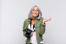 Middle Age Woman Looking Surprised And Shocked, With Jaw Dropped Holding An Object With An Open Hand On The Side. Photographer Concept