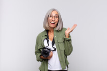 Middle Age Woman Feeling Happy, Surprised And Cheerful, Smiling With Positive Attitude, Realizing A Solution Or Idea. Photographer Concept
