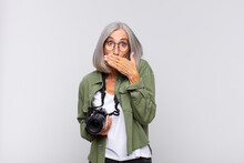 Middle Age Woman Covering Mouth With Hands With A Shocked, Surprised Expression, Keeping A Secret Or Saying Oops. Photographer Concept