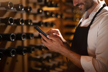 Modern Farmer Or Winemaker Is Using Winery Online Commerce Applications On A Smartphone For Checking Customer Service And Selling Orders Summary Of His Wine Production In A Wine Cellar.