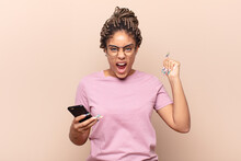 Young Afro Woman Shouting Aggressively With An Angry Expression Or With Fists Clenched Celebrating Success. Smart Phone Concept