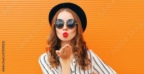 Fotografering Portrait of stylish woman model blowing red lips sending sweet air kiss wearing