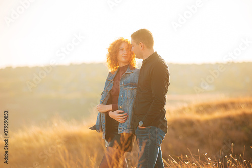 Fototapeta A beautiful couple walking and having time together on a field obraz