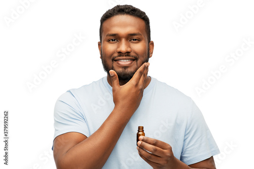 grooming and people concept - smiling young african american man applying lotion or beard oil over white background
