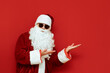 Santa Claus in sunglasses shows hands aside on empty space isolated on red background. Santa and encourages pointing to Copyspace. X mas concept