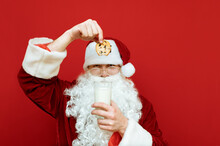 Portrait Of A Serious Santa Claus Standing On A Red Background And Throwing Cookies Into A Glass Of Milk, Looking Suspiciously At The Camera. Santa And Christmas Cookies With Milk. Isolated.