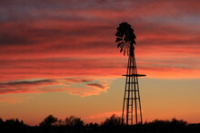 Silhouette Of A Windmill At Sunset With A Red Sky North Of Hutchinson Kansas USA Out In The Country.