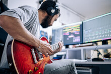 Young Musician Playing Electric Guitar With Headphones At Home Studio. Music And Professional Musicians Concept