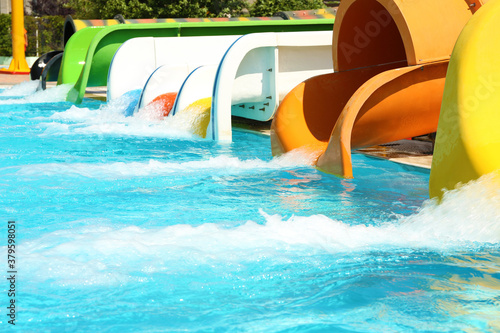 Fototapeta Different colorful slides and swimming pool in water park on sunny day obraz