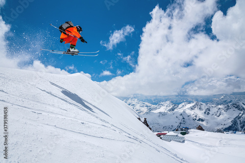 Valokuva Man skier athlete makes a jump in flight on a snowy slope against the backdrop of a blue sky of mountains and clouds