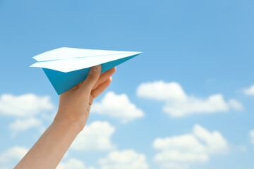 Woman holding paper plane against blue sky, closeup. Space for text