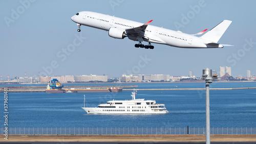 青空を背景に羽田空港を離陸するジャンボジェットと海を航行する客船 Canvas Print