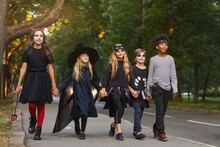Full Length Portrait Of Multi-ethnic Group Of Kids Walking In Street While Trick Or Treating On Halloween