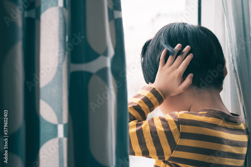 Fototapeta Little Asian boy stand by window, cry and cover ears feeling fear, insecure, anxiety and stress. Domestic Violence, Autism disorder spectrum awareness and Childhood mental disorders problem concept. obraz