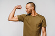 Close up portrait of a happy african american man wearing t-shirt flexing bicep arm muscle