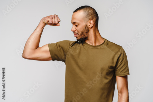 Fotografie, Obraz Close up portrait of a happy african american man wearing t-shirt flexing bicep