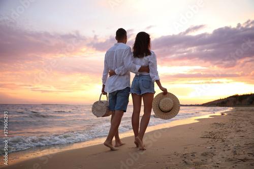Fototapeta Lovely couple walking on beach at sunset, back view obraz