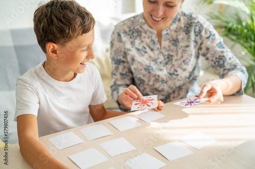 Valokuva 7-year-old boy plays a memory Board game with his mother to develop memory