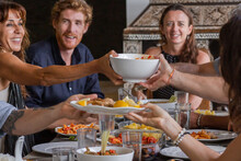 Diverse Group Of Multiethnic Friends Enjoying Meal Sharing And Passing Food To Each Other In Outdoor Cafe Or Home. Leisure, Food And Drinks, People And Holidays Concept