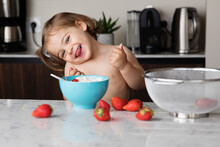 Happy Toddler Girl In Kitchen Eating Strawberries And Cream
