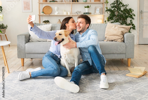 Fototapeta Young couple taking selfie with their dog in living room obraz