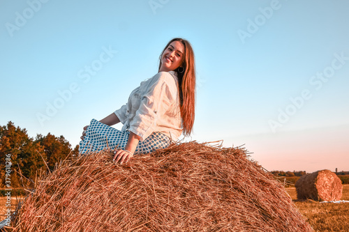 Photo Portrait of young sexy woman on the haystack in morning sunlight, countryside