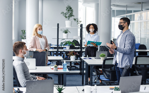Fotografia Corporate meeting in office, multiracial workers in protective masks discussion