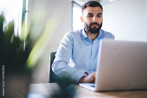 Foto Confident millennial bearded businessman typing on laptop computer sitting at wo