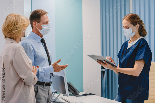 Fototapeta Caucasian middle aged couple having consultation and appointment in protective medical face masks at reception in clinic obraz