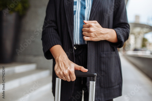Fototapeta Close up of a professional business woman standing near the hotel's doors with a suitcase waiting for a taxi. Business trip and official look. Work and travel concept. obraz
