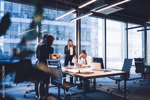 Fototapeta Thoughtful team of colleagues using gadgets during meeting obraz na płótnie