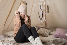 A Young Woman Plays With Her Knitted Hat While Sitting In A Cozy Teepee. The Young Woman Hides Her Eyes Under Her Hat And Laughs.