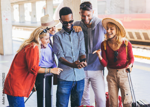 Fototapeta Multiracial group of friends wearing face mask using smartphone at train railway station. Young people booking online service transportation. obraz