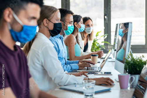Successful concentrated business team wearing a hygienic facial mask while working together in the office keeping safe distances on coworking place.