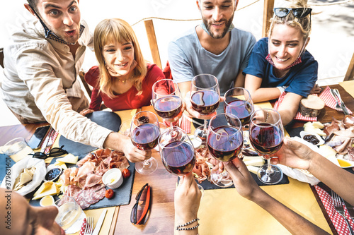 Friends toasting red wine at restaurant bar with open face masks - New normal lifestyle concept with happy people having fun together at tavern - Bright warm filter with focus on glasses