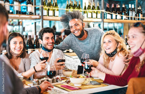 Obraz Friends drinking red wine at sushi bar restaurant with open face masks - New normal lifestyle concept with happy people having fun together on vivid filter - Focus on afroamerican guy - fototapety do salonu