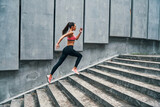 Fototapeta Na drzwi - Full length of young woman in sports clothing jogging while exercising on the steps outdoors