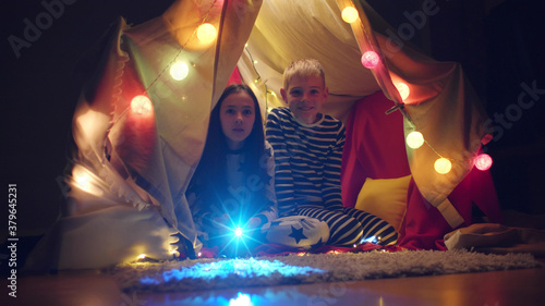 Valokuva Brother and sister watching cartoons using projector sitting in wigwam