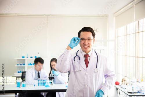 Fényképezés Team of chemists working in the lab Asian  doctor holding Covid-19 or coronaviru