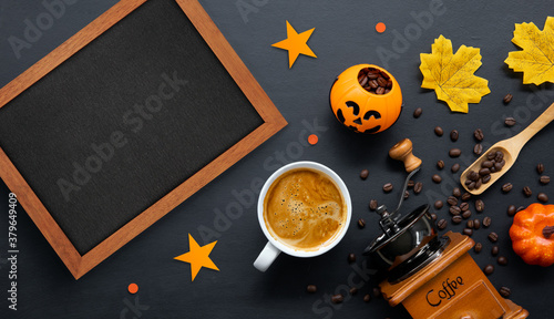 halloween decoration with hot coffee and beans on dark background. flat lay. Copy space for text.